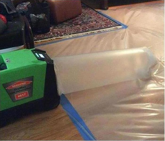 SERVPRO equipment connected to a plastic tube and plastic covering the floor