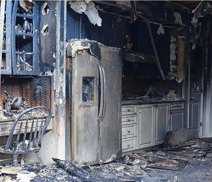 Kitchen with cabinets and refrigerator burned and covered in soot and debris covering the floor