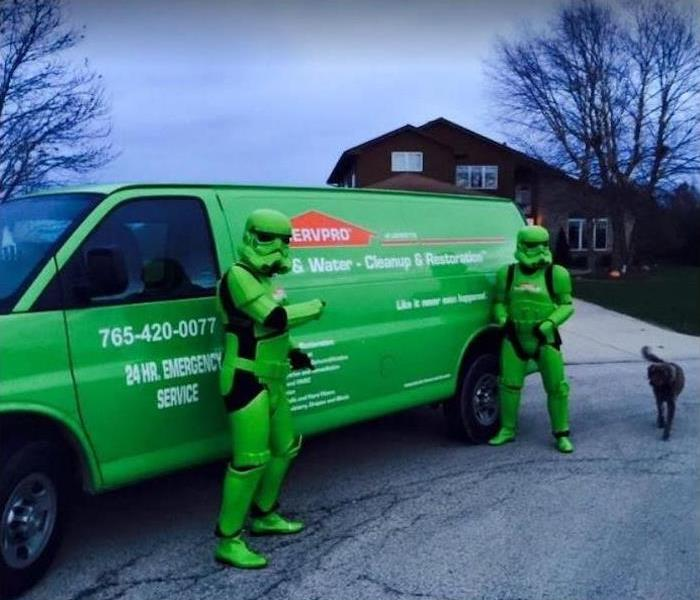 SERVPRO technicians dressed as superheroes standing in front of a SERVPRO van.