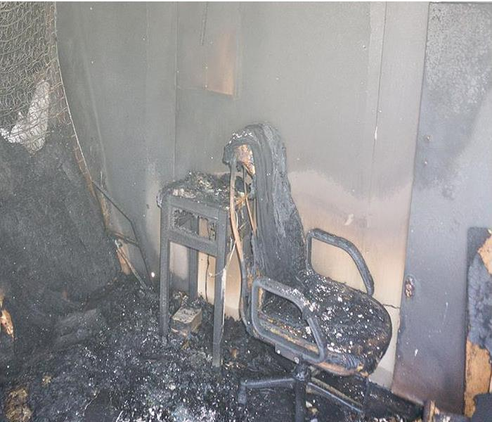 furniture in room burned after fire with soot and dust