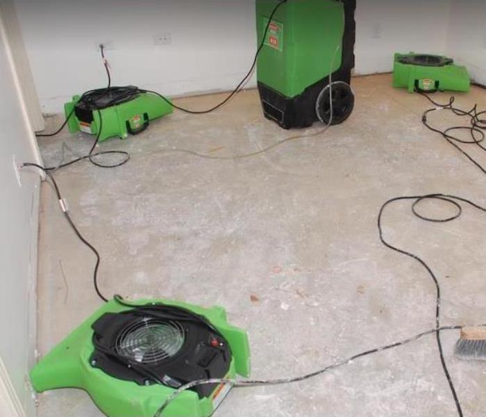 Fans and dehumidifiers running in a bedroom with a concrete floor