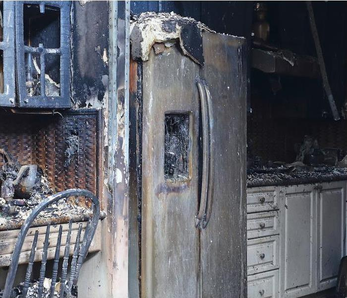 residential kitchen with burned fridge and cabinets. Soot covering the counters and walls
